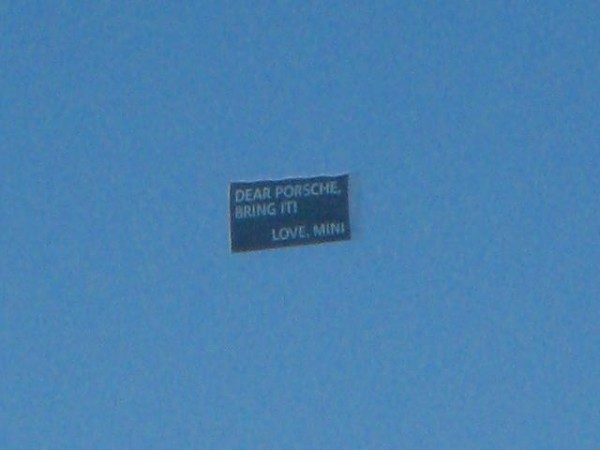 plane flying a banner that reads Dear Porsche, Bring It.  Love, Mini