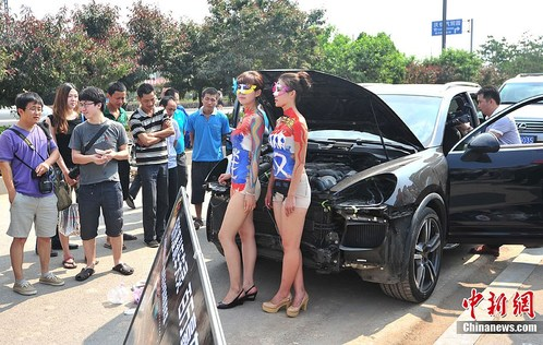 Chines girls in body paint posing with Porsche Cayenne