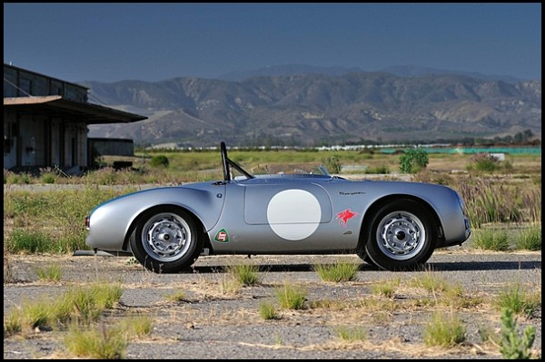 a Porsche 550 Spyder in weed covered field
