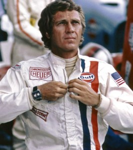 Steve McQueen zipping his Gulf racing suit wearing a Tag Monaco