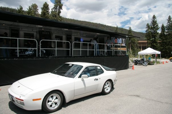 White Porsche 944 in front of a Mobil1 Display Trailer
