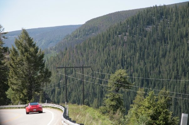 Guards red Porsche 997 C4S driving in Mountains of CO
