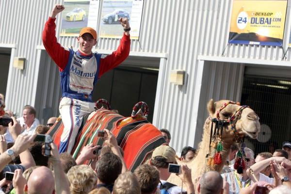 Marco Holzer riding a camel in celebration of winning the Dubai 24