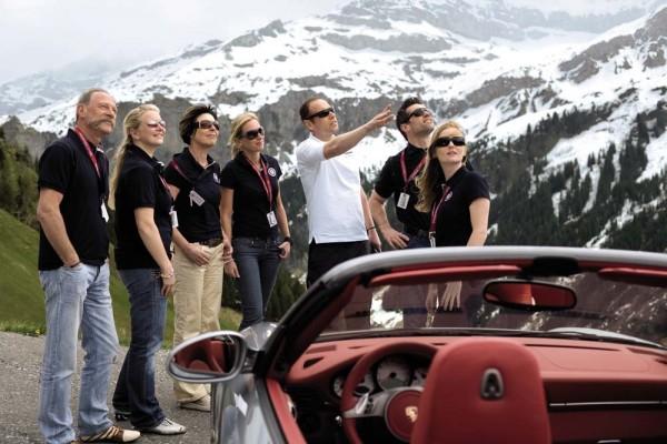 participants in the porsche travel club surveying a scenic vista
