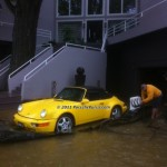 porsche being rolled onto uninflated bladder before river floods