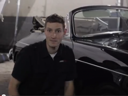 Larry from AMMOnyc sitting next to a Porsche 356