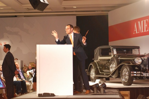 The auctioneer works the crowd during the sale of the Porsche 908/3