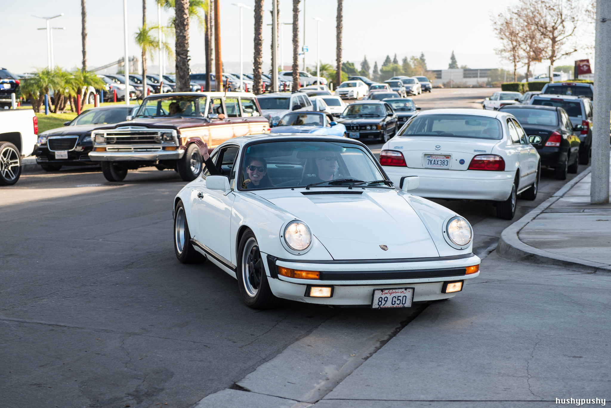White 1989 Carrera 3.2 pulls into Radwood 2 as the passenger waves to the camera