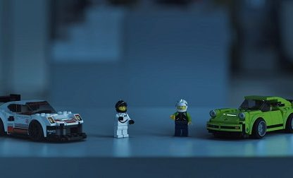 two lego action figures and their Porsche speed champion rides