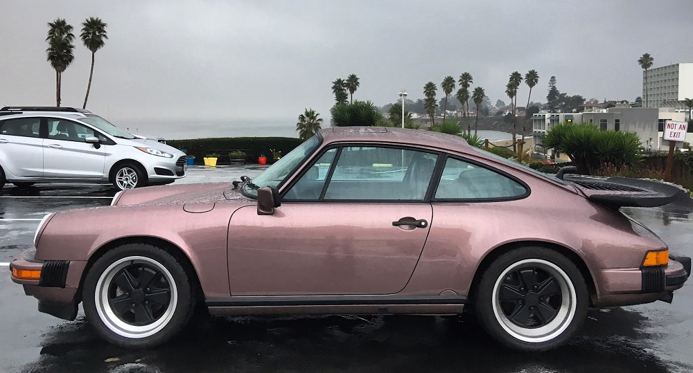 Porsche 911 in Cassis Red sitting in a wet parking lot