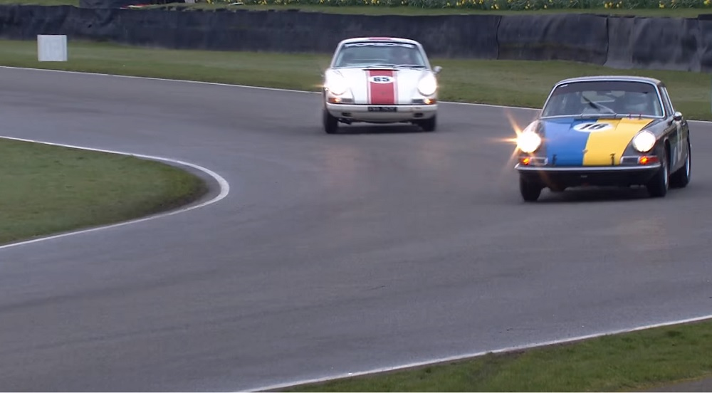 Two early Porsche 911s chase each other on the Goodwood circuit