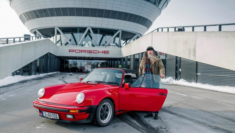 Magnus walker standing next to a Porsche 930 at Leipzig