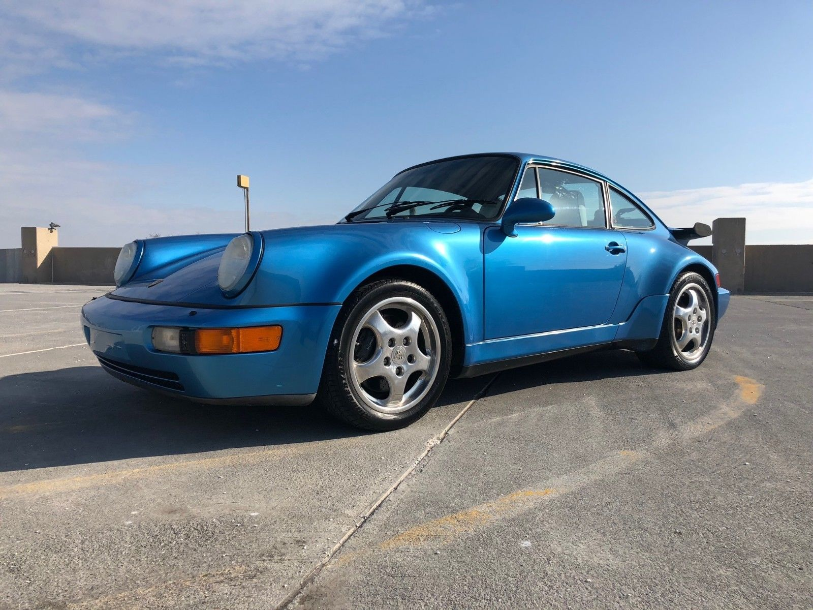 Blue Porsche 964 Turbo on a parking deck for sale