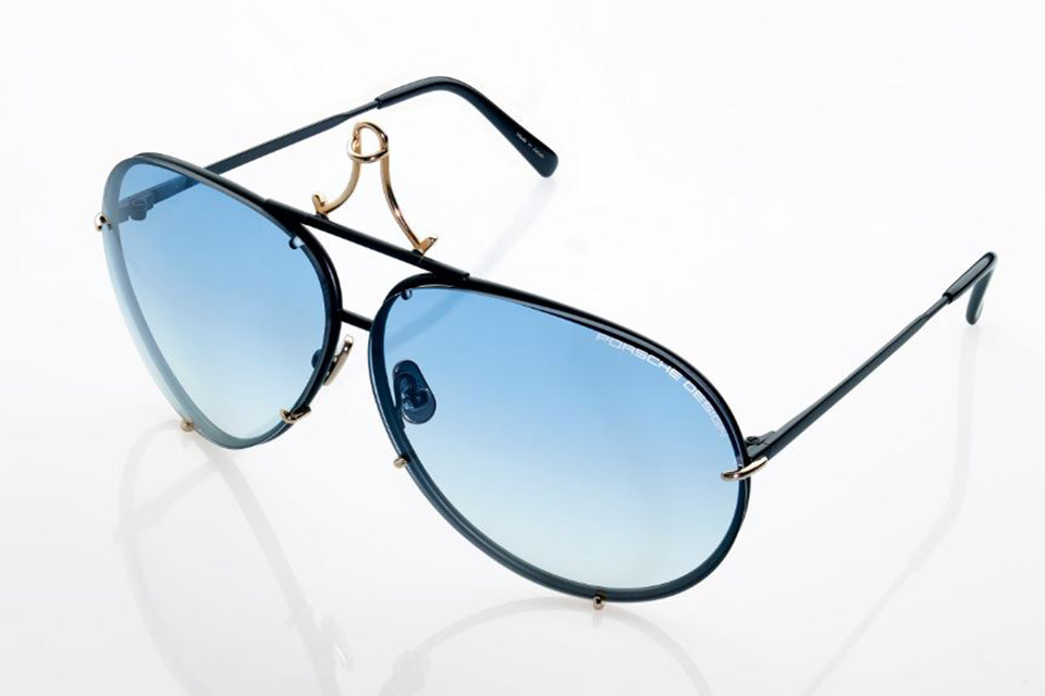 Porsche Design aviator-style sunglasses with gold accent on a black frame and blue shaded lenses.